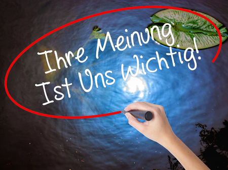 solicitation: Woman Hand Writing Ihre Meinung Ist Uns Wichtig! (Your Opinion is Important to Us in German) with marker on visual screen. Isolated on nature. Business concept. Stock Photo