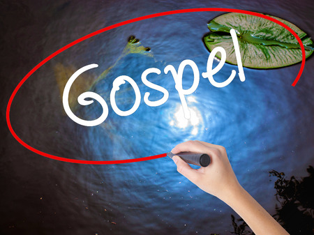 working ethic: Woman Hand Writing Gospel  with marker over transparent board. Isolated on nature. Business concept. Stock Photo