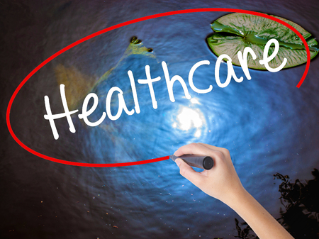mandated: Woman Hand Writing Healthcare with marker over transparent board. Isolated on nature. Business concept. Stock Photo
