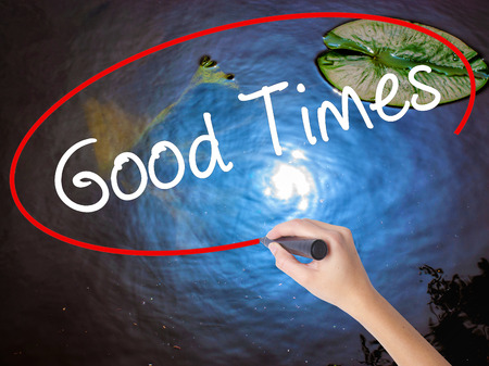 good times: Woman Hand Writing Good Times with marker over transparent board. Isolated on nature. Business concept. Stock Photo