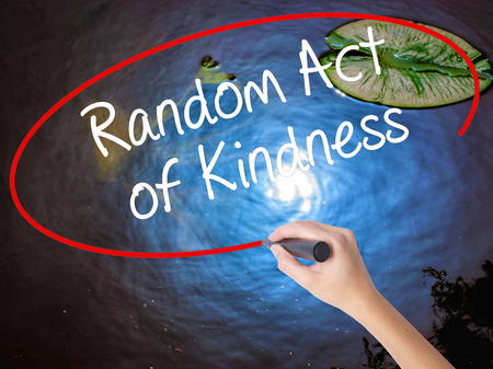 helping others: Woman Hand Writing Random Act of Kindness with marker over transparent board. Isolated on nature. Business concept. Stock Photo
