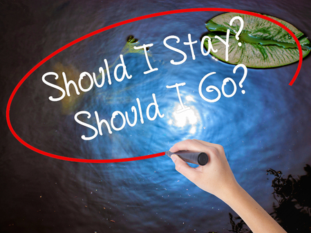 indecisiveness: Woman Hand Writing Should I Stay? Should I Go? with marker over transparent board. Isolated on nature. Business concept. Stock Photo