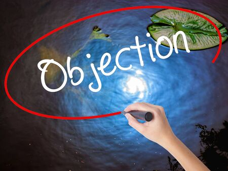 Woman Hand Writing Objection with marker over transparent board. Isolated on nature. Business concept. Stock Photo