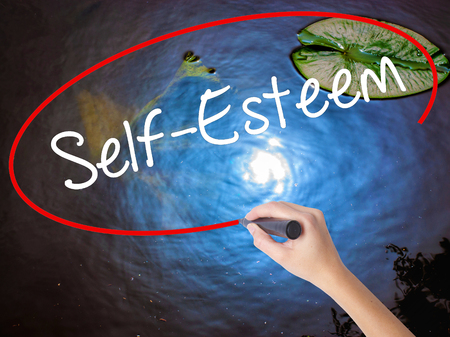 self worth: Woman Hand Writing Self-Esteem with marker over transparent board. Isolated on nature. Business concept. Stock Photo
