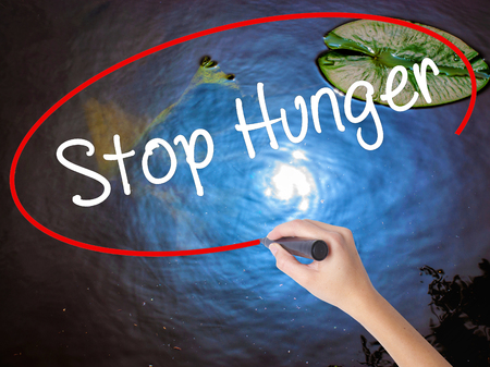 dearth: Woman Hand Writing  Stop Hunger with marker over transparent board. Isolated on nature. Business concept. Stock Photo Stock Photo