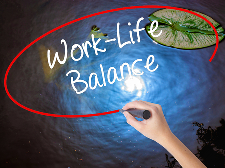 health equity: Woman Hand Writing Work-Life Balance with marker over transparent board. Isolated on nature. Business concept. Stock Photo