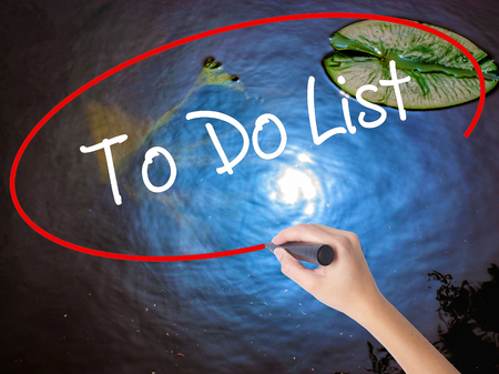 todo list: Woman Hand Writing To Do List with marker over transparent board. Isolated on nature. Business concept. Stock Photo Stock Photo