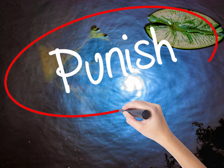 enforcing the law: Woman Hand Writing Punish with marker over transparent board. Isolated on nature. Business concept. Stock Photo