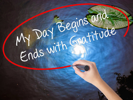 begins: Woman Hand Writing My Day Begins and Ends with Gratitude with marker over transparent board. Isolated on nature. Business concept. Stock Photo