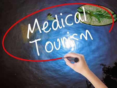health care fees: Woman Hand Writing Medical Tourism with marker over transparent board. Isolated on nature. Business concept. Stock Photo