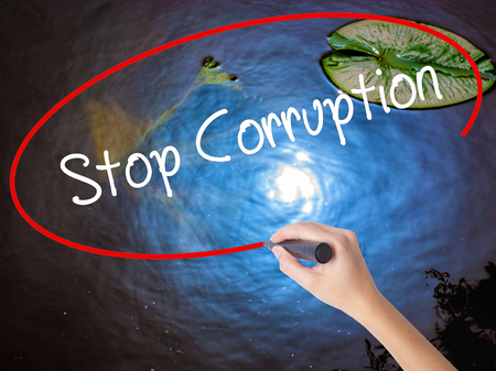sinner: Woman Hand Writing Stop Corruption with marker over transparent board. Isolated on nature. Business concept. Stock Photo