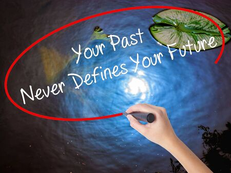 defines: Woman Hand Writing Your Past Never Defines Your Future with marker over transparent board. Isolated on nature. Business concept. Stock Photo