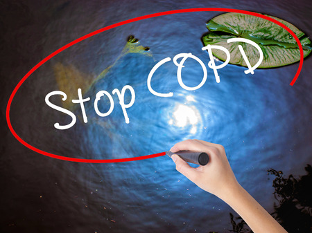 Woman Hand Writing Stop COPD with marker over transparent board. Isolated on nature. Business concept. Stock Photo