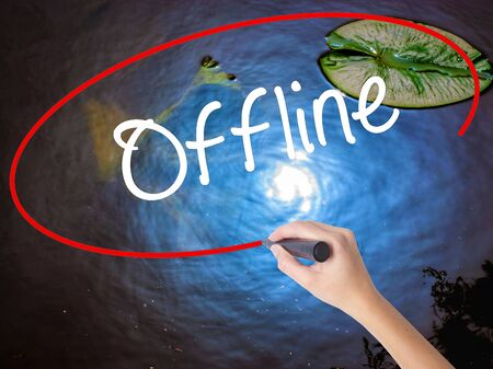Woman Hand Writing Offline  with marker over transparent board. Isolated on nature. Business concept. Stock Photo