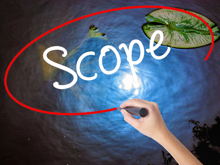 Woman Hand Writing Scope with marker over transparent board. Isolated on nature. Business concept. Stock Photo