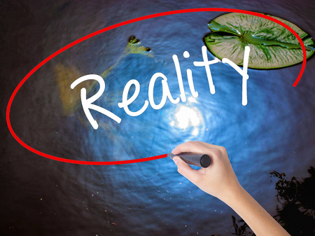 Woman Hand Writing  Reality with marker over transparent board. Isolated on nature. Business concept. Stock Photo