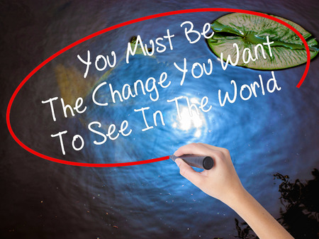 helping others: Woman Hand Writing You Must Be The Change You Want To See In The World with marker over transparent board. Isolated on nature. Business concept. Stock Photo