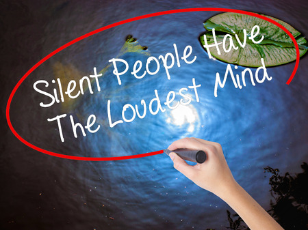 Woman Hand Writing Silent People Have The Loudest Mind with marker over transparent board. Isolated on nature. Business concept. Stock Photo