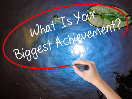 overachieving: Woman Hand Writing What Is Your Biggest Achievement? with marker over transparent board. Isolated on nature. Business concept. Stock Photo