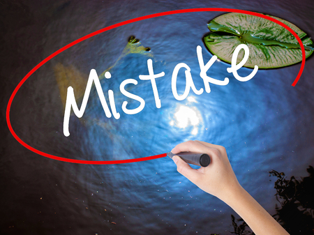 Woman Hand Writing Mistake with marker over transparent board. Isolated on nature. Business concept. Stock Photo Stock Photo