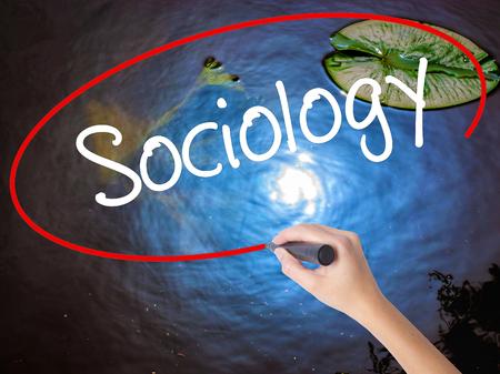 sociologia: Mujer escritura de la mano con marcador Sociología por la borda transparente. Aislado en la naturaleza. Concepto de negocio. Foto de stock Foto de archivo