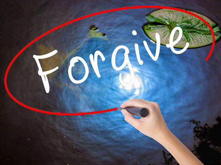 remorse: Woman Hand Writing Forgive with marker over transparent board. Isolated on nature. Business concept. Stock Image Stock Photo