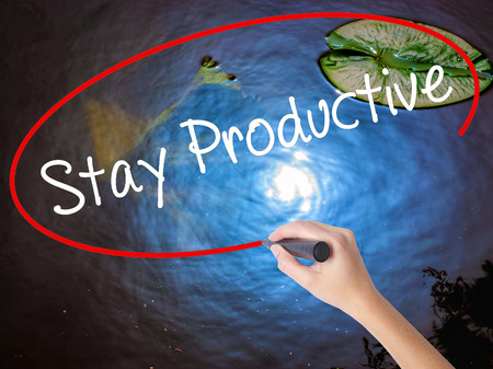 Woman Hand Writing Stay Productive with marker over transparent board. Isolated on nature. Business concept. Stock Photo