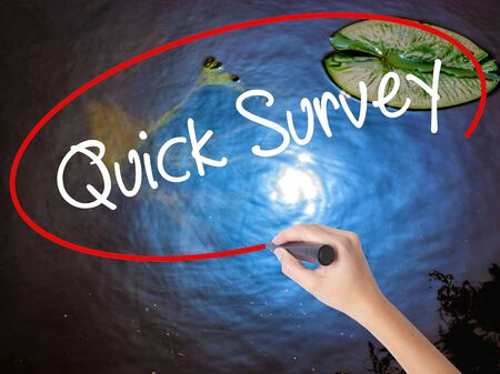Woman Hand Writing Quick Survey with marker over transparent board. Isolated on nature. Business concept. Stock Photo