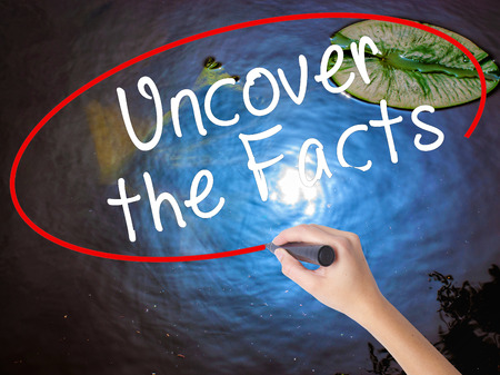 uncover: Woman Hand Writing Uncover the Facts with marker over transparent board. Isolated on nature. Business concept. Stock Image