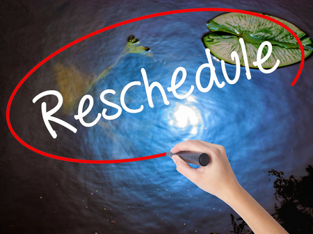 Woman Hand Writing Reschedule  with marker over transparent board. Isolated on nature. Business concept. Stock Photo Stock Photo