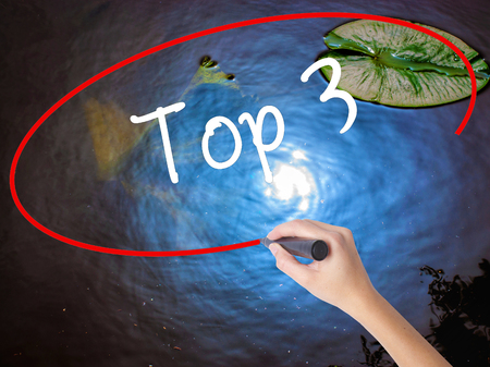Woman Hand Writing Top 3 with marker over transparent board. Isolated on nature. Business, technology, internet concept. Stock Photo