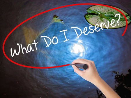 Woman Hand Writing What Do I Deserve? with marker over transparent board. Isolated on nature. Business concept. Stock Photo