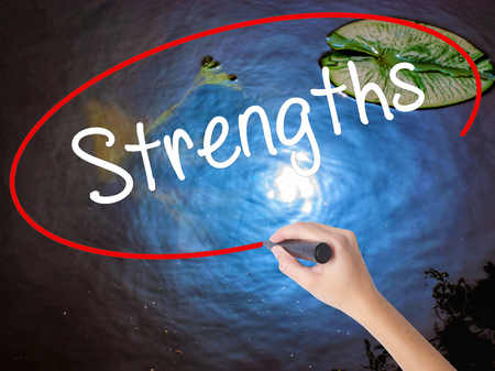appraise: Woman Hand Writing Strengths with marker over transparent board. Isolated on nature. Business concept. Stock Photo