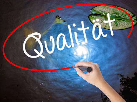Woman Hand Writing Quality (Qualitat in German) with marker over transparent board. Isolated on nature. Business concept. Stock Photo
