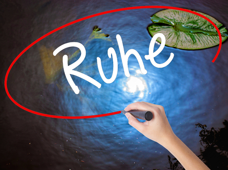 Woman Hand Writing Ruhe (Quiet in German) with marker over transparent board. Isolated on nature. Business concept. Stock Photo