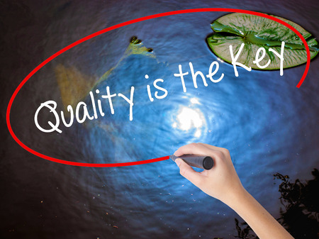 Woman Hand Writing Quality is the Key with marker over transparent board. Isolated on nature. Business, technology, internet concept. Stock Photo