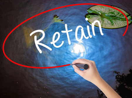 retained: Woman Hand Writing Retain with marker over transparent board. Isolated on nature. Business concept. Stock Photo Foto de archivo