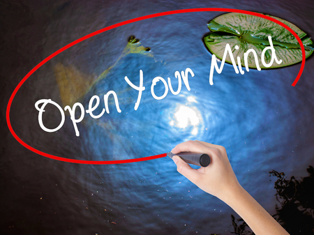 Woman Hand Writing Open Your Mind with marker over transparent board. Isolated on nature. Business concept. Stock Photo