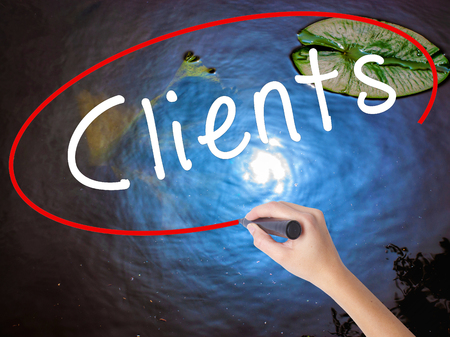 Woman Hand Writing Clients with marker over transparent board. Isolated on nature. Business concept. Stock Image