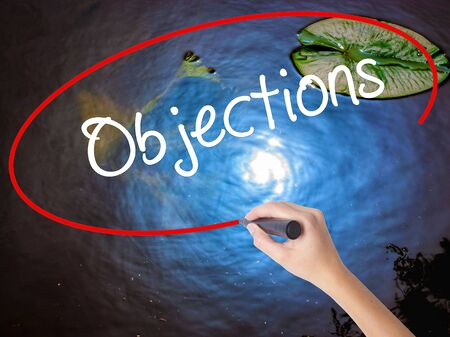 persuasive: Woman Hand Writing Objections  with marker over transparent board. Isolated on nature. Business concept. Stock Photo