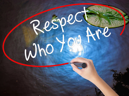 Woman Hand Writing Respect Who You Are with marker over transparent board. Isolated on nature. Business concept. Stock Photo