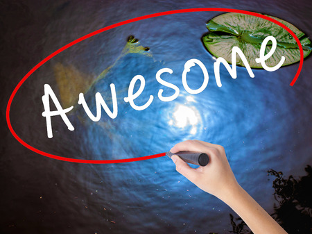 Woman Hand Writing Awesome with marker over transparent board. Isolated on nature. Business concept. Stock Image