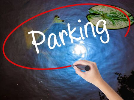 Woman Hand Writing Parking with marker over transparent board. Isolated on nature. Business concept. Stock Photo