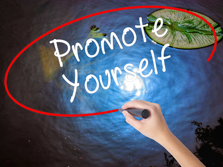 promote: Woman Hand Writing Promote Yourself with marker over transparent board. Isolated on nature. Business concept. Stock Photo