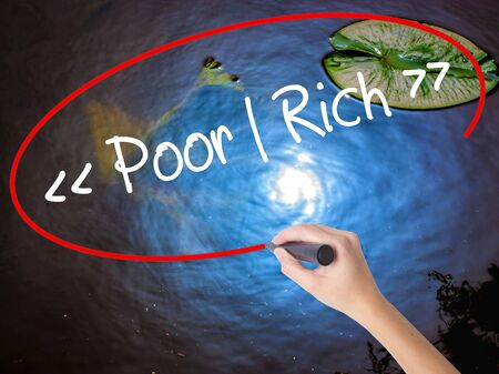 impoverished: Woman Hand Writing Poor - Rich with marker over transparent board. Isolated on nature. Business concept. Stock Photo