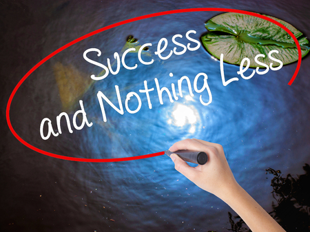 nothing: Woman Hand Writing Success and Nothing Less with marker over transparent board. Isolated on nature. Business concept. Stock Photo