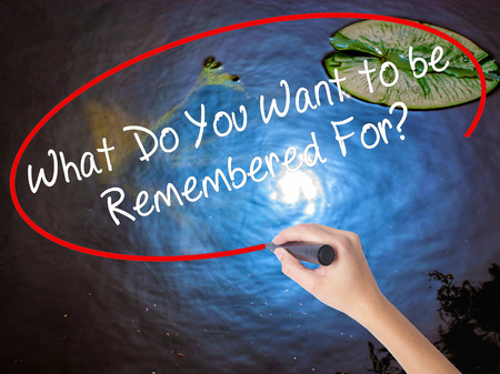 remembered: Woman Hand Writing What Do You Want to be Remembered For? with marker over transparent board. Isolated on nature. Business concept. Stock Photo Stock Photo