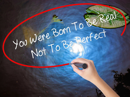 true born: Woman Hand Writing You Were Born To Be Real Not To Be Perfect with marker over transparent board. Isolated on nature. Business, technology, internet concept.