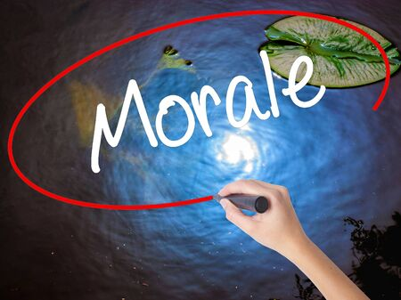 Woman Hand Writing Morale with marker over transparent board. Isolated on nature. Business concept. Stock Photo