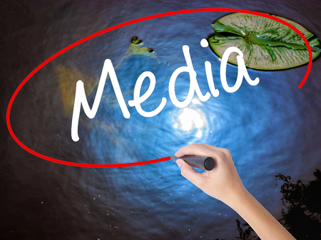 Woman Hand Writing Media with marker over transparent board. Isolated on nature. Business concept. Stock Photo Stock Photo